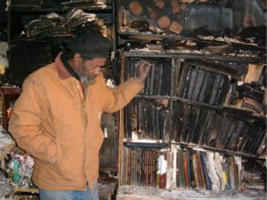 Mixed media artist Gregory Warmack (aka Mr. Imagination) surveys the 2008 fire damage at his Bethlehem, PA home and studio. (photo credit: Greg Heller-Labelle) (NOTE: Mr I passed away in 2012)
